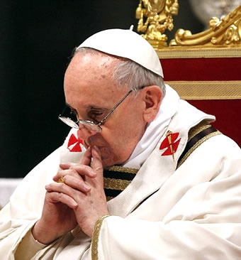 Pope Francis sits in chair while praying
