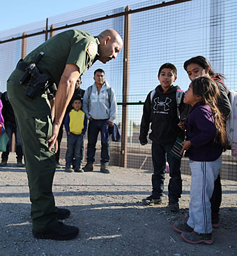 U.S. Border Patrol agent speaks with little immigrant children at U.S. Mexico Border fence