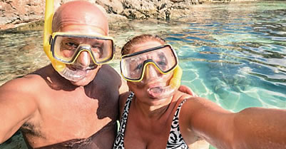 Elderly Latino couple scuba diving in blue waters